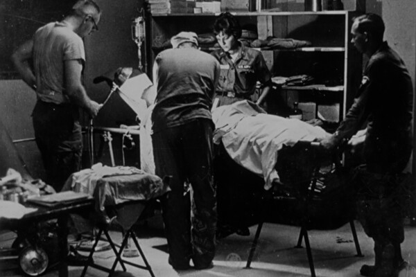 A black-and-white image of health care professionals standing around a patient in a surgical suite during the Vietnam War.