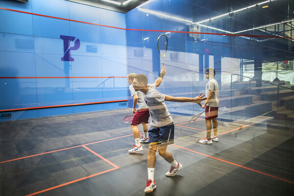 Inside one of the fancy new glass courts at Penn's revitalized Penn Squash Center, three men play squash.
