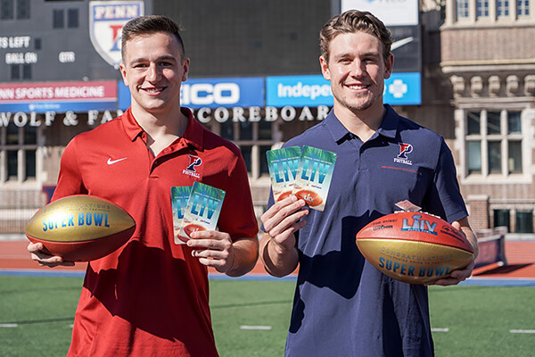 Anthony Lotti and Sam Philippi hold tickets to the Super Bowl in one hand and footballs in the other on a football field.