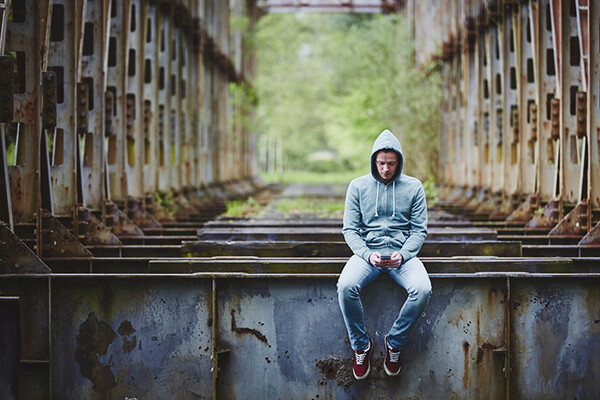 Person wearing a hoodie sits on a structural beam alone in an isolated area holding a smartphone.
