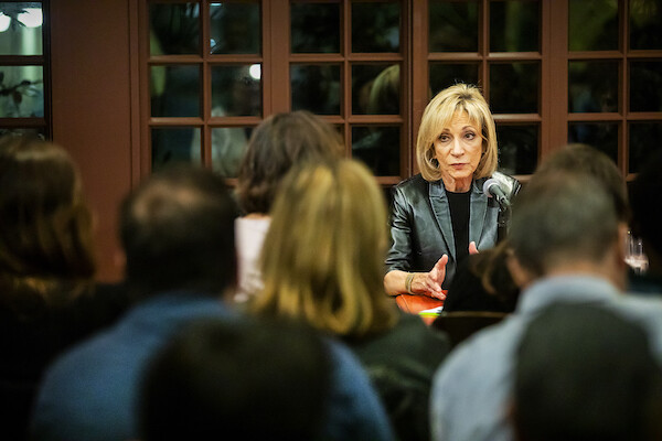 NBC's chief foreign affairs correspondent Andrea Mitchell sits at a table in front of a microphone, responding to a question at Kelly Writers House on Penn's campus, as audience members look on.