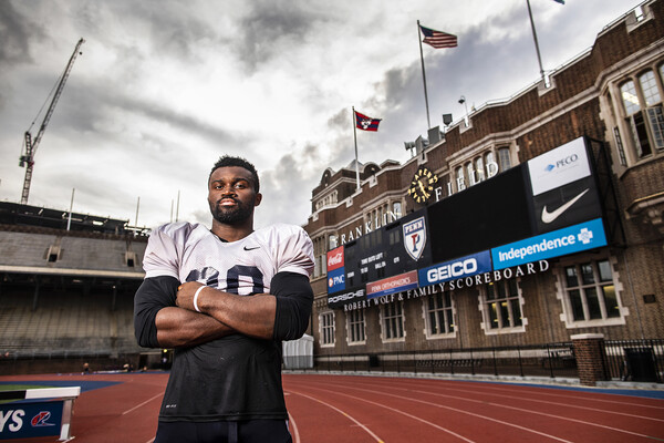 In his shoulder pads, Karekin Brooks of the Penn football team poses with his arms folded on the track at Franklin Field.