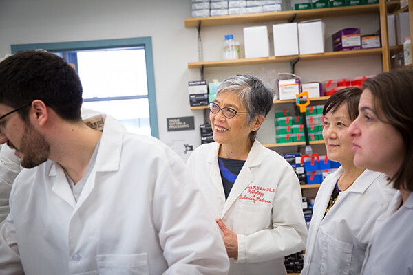 Virginia Lee stands smiling in a lab surrounded by three colleagues
