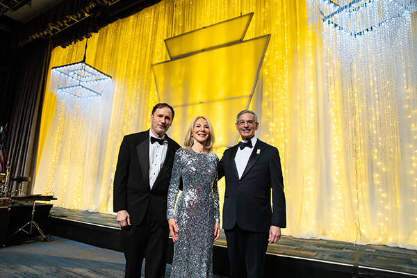 Penn president Amy Gutmann on stage at Pennsylvania Society Award dinner with husband and xxxx
