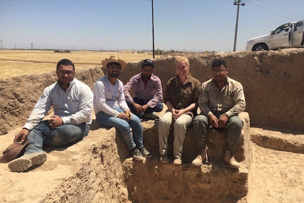 Five people sit along ancient mud walls at an archeological dig in Iraq.