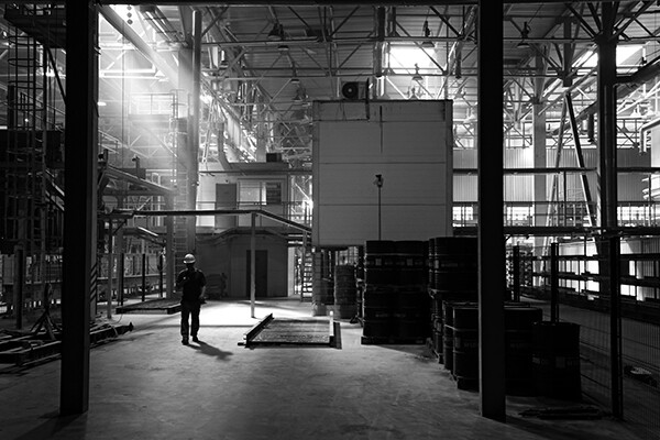 One factory worker in a hard hat walking alone on a factory floor.
