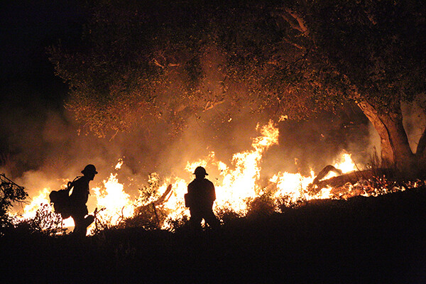 Fire crews tend to a using controlled burns at night to prevent further uncontrolled fires