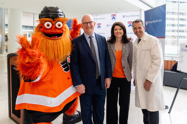 Philly Flyers' mascot Gritty waves while standing beside Kevin Mahoney, Valerie Camillo, President of Business Operations for the Philadelphia Flyers & Wells Fargo Center and Penn Medicine's Brian Sennett.