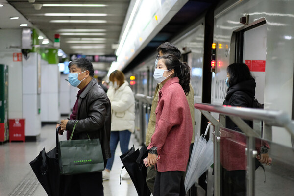 People in a subway station in Shanghai wearing surgical masks. One is carrying two bags, another is carrying a phone, a third is holding an umbrella.