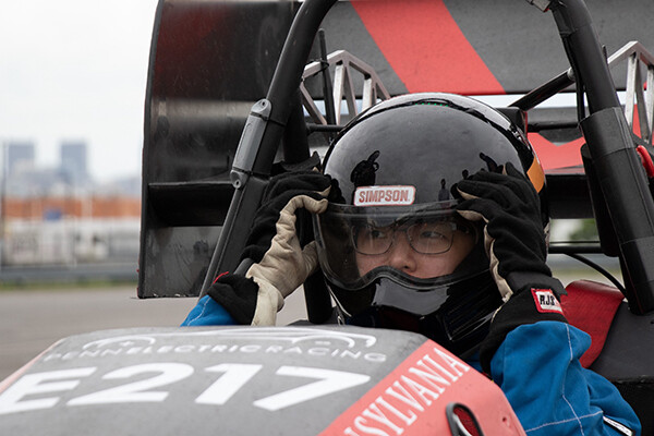 Kathie Jin adjusts her helmet inside a Penn Electric Racing car.