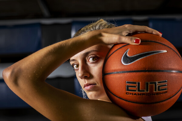 At the Palestra, Kendall Grasela of the women's basketball team poses with a ball resting on her shoulder.