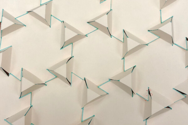 a pattern of raised triangles made out of paper with blue lines indicating flaps that reach out to neighboring structures