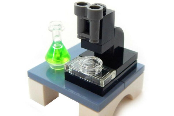 a lego set of a microscope on a table with a green vial next to it