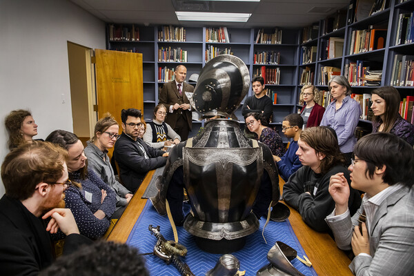 students gathered around a table looking at armor