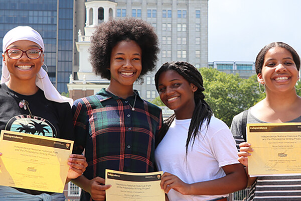 Four students hold certificates from Philadelphia Writing Project smiling and standing outdoors
