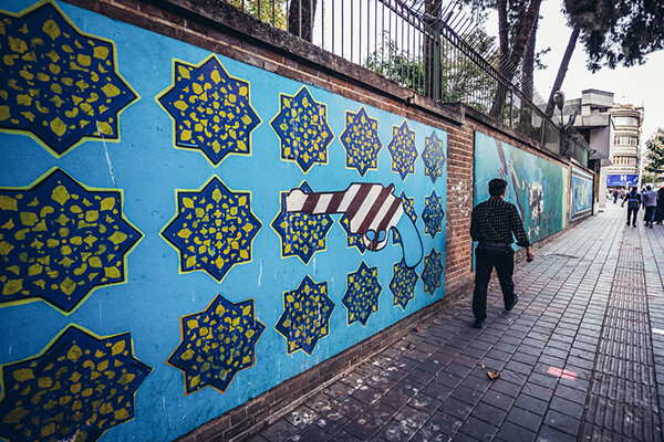 Pedestrian on the sidewalk walking past the wall of the former US embassy in Tehran.