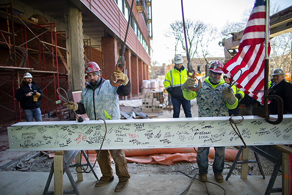 Two construction workers attach a crane to wires around a beam covered in signatures at the topping-off ceremony for New College House West