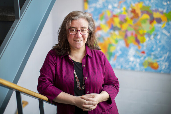 woman with clasped hands stands in a stairwell with colorful art in the background