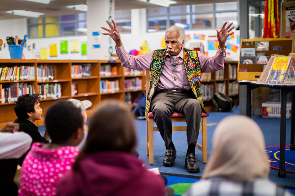 Ashley Bryan gestures with his hands open at a library at an elementary school reading his books to children seated on the ground.