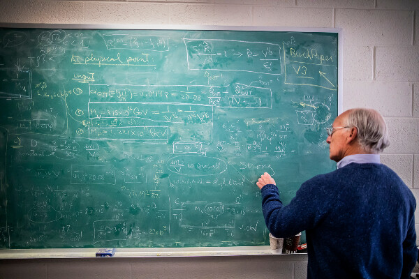 a person standing in front of a chalkboard covered in equations