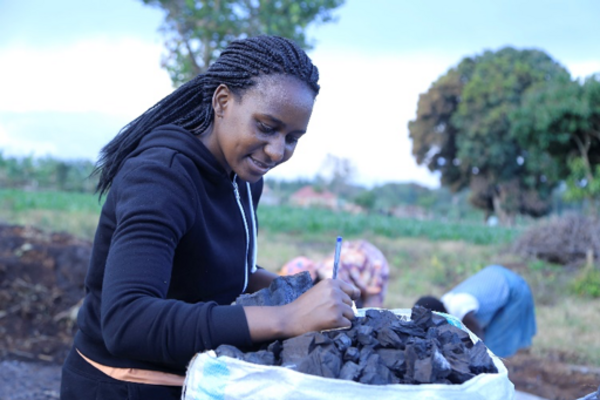 Penn alumna Catherine Nabukalu examines a bag of charcoal as two people work in a field in the background