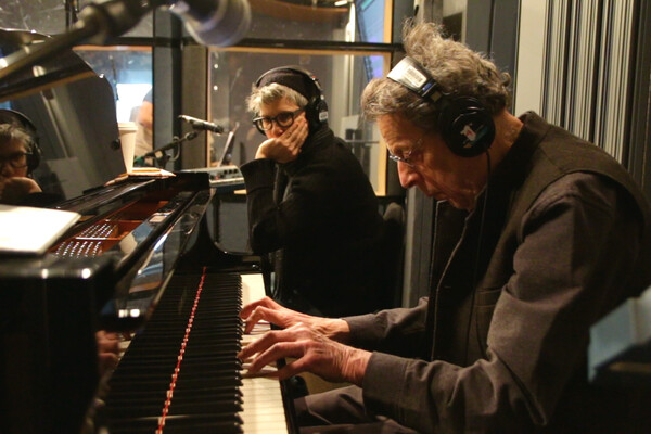 Philip Glass at piano with headphones