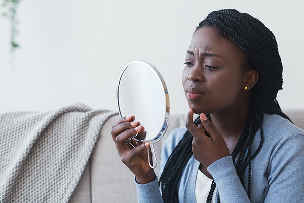 A Black person examines their skin for acne in a hand mirror.