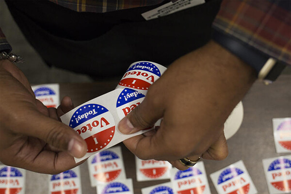 African American person tearing off an I Voted Today sticker