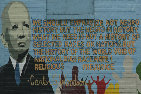 "Mural of Carter G. Woodson on a brick wall with a quote reading ""We should emphasize not Negro history but the Negro in history. What we need is not a history of selected races or nations, but the history of the world void of national bias, race, hate and religious prejudice."""