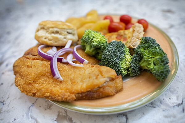 Plate of food with fried fish, crab pie, butter biscuit, broccoli, and tomatoes.