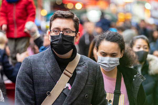 Two people outside in a public crowd wearing face masks