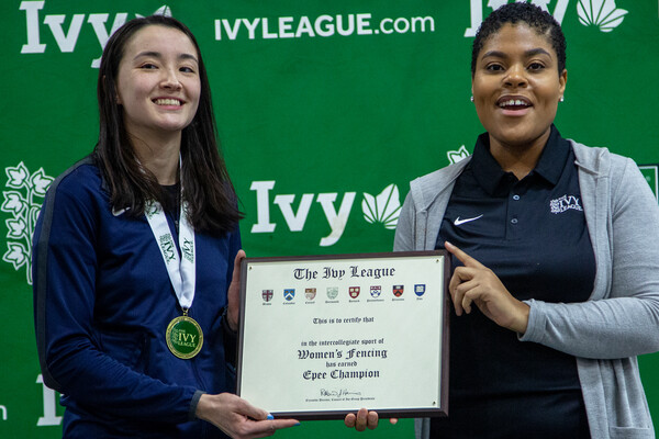 Chloe Daniel, left, receives a plaque celebrating her Ivy League individual epee championship from an Ivy League official.