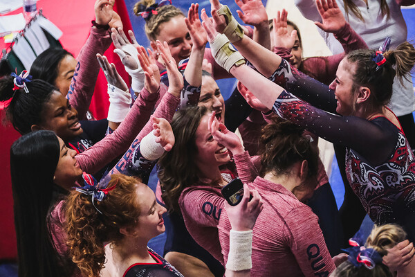 Members of the gymnastics team high-five and celebrate during a meet.