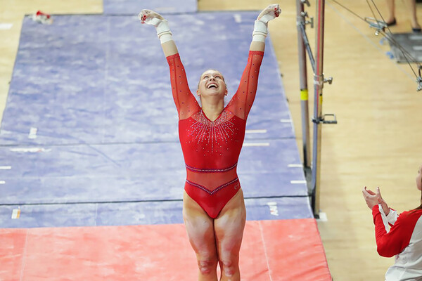 McCaleigh Marr, a freshman on the gymnastics team, raises her arms in the air and smiles after finishing an event.