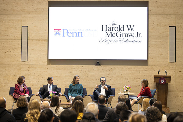Five people sit on a stage in discussion with an audience in front, on projection on wall behind them reads The Harold W. McGraw, Jr. Prize in Education