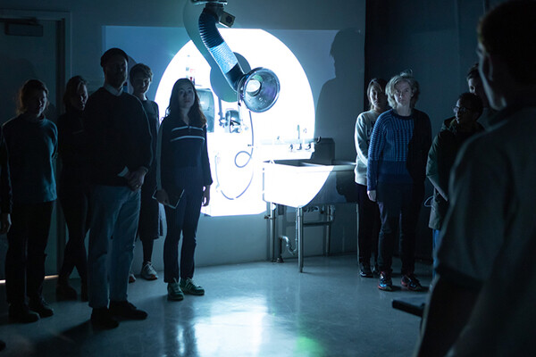 group in front of screen with light projected on it