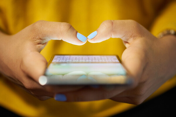 Hands holding smartphone with fingers poised over screen