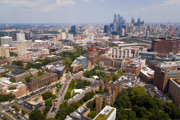 Aerial view of Penn campus buildings with Philadelphia skyline in background.