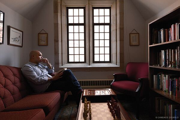 University minister sitting on a sofa in his office by a window.