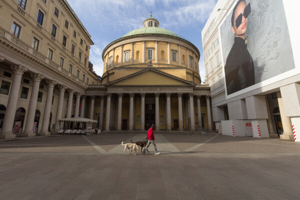 A person with two dogs walking in front of an empty plaza in front of the Cathedral of San Carlo al Corso in Milan, Italy