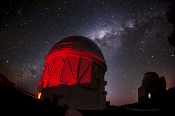 a telescope dome bathed in red light with the milky way galaxy behind it