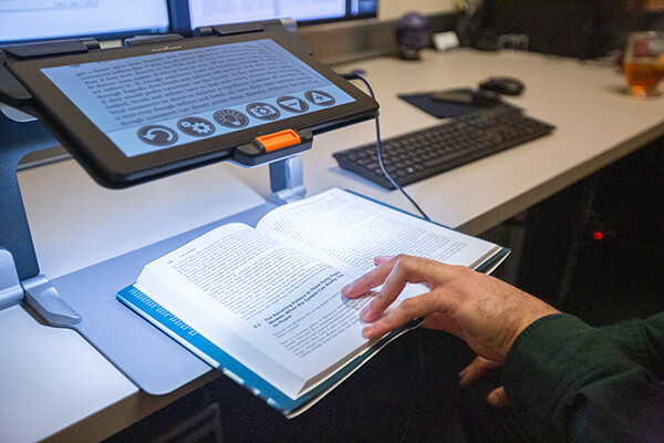 A hand on an open book attached to an assisted reading computer at the Weingarten assisted learning center