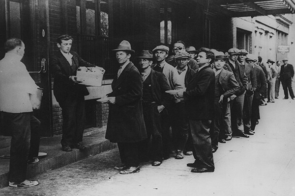 A long line of people waiting to in a bread line in New York City during the Great Depression in 1932