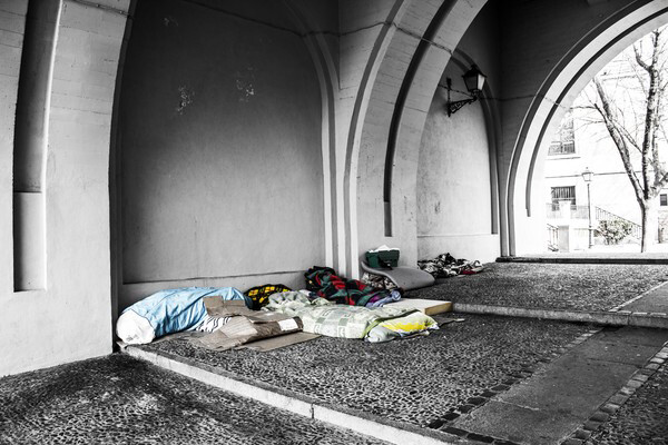 Bedding and blankets belonging to homeless people on the ground underneath an underpass