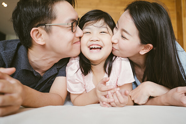 Asian parents kiss their child