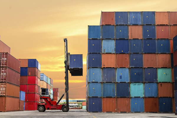 Colorful shipping containers piled high, with one being loaded by a truck.