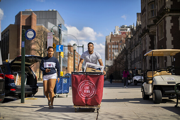 Two Penn students walk down a sidewalk on campus, one pushes a move-out cart.