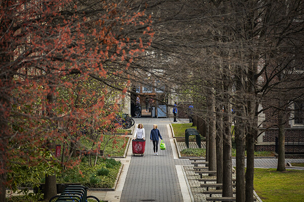 Two people walk through Locust Walk, one pushing a move-out cart.