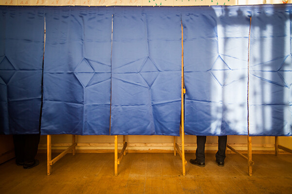 One person voting behind a curtain in one of a row of three voting booths