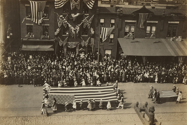 Parade from 1918 in the streets with people carrying a large American flag